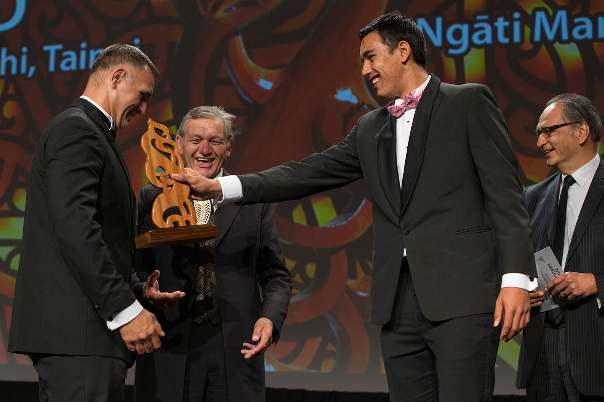Tai Hikuroa Wynyard (R) hands the trophy to his father, Jason, as they share the Albie Pryor Memorial Maori Sportsperson of the Year presented by the Maori King Kiingi Tuheitia (C) at the Maori Sports Awards 2014, Vodafone Events Centre, Manukau, Auckland, New Zealand, Saturday, November 29, 2014. Photo: David Rowland/Photosport