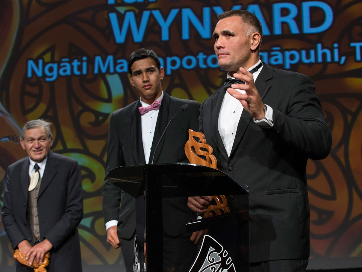 Tai Hikuroa Wynyard (C) watches his father, Jason speak, as they share the Albie Pryor Memorial Maori Sportsperson of the Year presented by the Maori King Kiingi Tuheitia (L) at the Maori Sports Awards 2014, Vodafone Events Centre, Manukau, Auckland, New Zealand, Saturday, November 29, 2014. Photo: David Rowland/Photosport