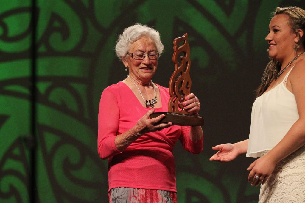 Taini Jamison accepts the trophy for her great uncle Jack Taiaroa from Desrae Temoana. Jack was inducted into the Maori Sports Hall of Fame at the 2013 Trillian Trust Maori Sports Awards at Vodafone Events Centre, Manukau. Photo: Fiona Goodall/photosport.co.nz